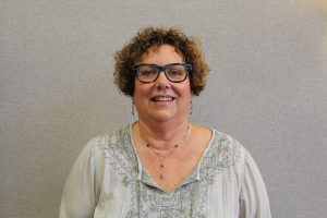 Curly hair lady with blue glasses and gray shirt